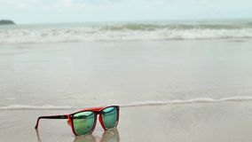 Sunglasses lying in sand on a beach. In a sunglasses reflected sea, waves and sky. Sunglasses lying in sand on a beach. In a sunglasses reflected sea, waves and stock video