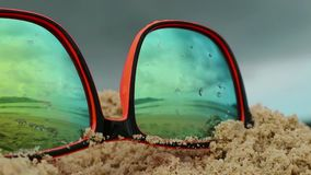 Sunglasses lying in sand on a beach. In a sunglasses reflected sea, waves and sky. Sunglasses lying in sand on a beach. In a sunglasses reflected sea, waves and stock video footage