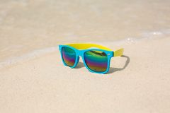 Sunglasses lying on sand. Sunglasses lying on sand with a reflection of the beach Royalty Free Stock Images