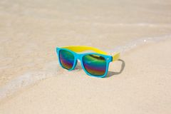 Sunglasses lying on sand. Sunglasses lying on sand with a reflection of the beach Stock Images