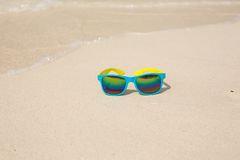 Sunglasses lying on sand. Sunglasses lying on sand with a reflection of the beach Royalty Free Stock Image