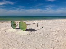 Sunglasses lying on a sandy beach getaway vacation royalty free stock images