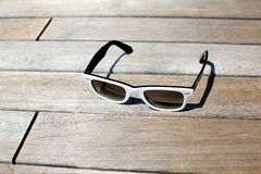 Sunglasses lying on the wooden deck, sunlit Royalty Free Stock Photos