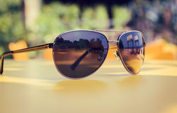 Sunglasses lying on a yellow table in a tropical beach cafe Royalty Free Stock Images