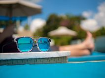Sunglasses, Men`s legs resting in a swimming pool background. Summer holiday traveling concept design banner with copyspace royalty free stock image