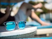 Sunglasses, Men`s legs resting in a swimming pool background. Summer holiday traveling concept design banner with copyspace stock image