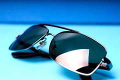 Sunglasses in metal frame with grey lenses on blue background stock photos