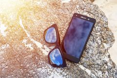 Sunglasses with mobile. Sunglasses with mobile on stone in beach Royalty Free Stock Image