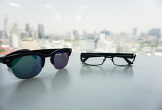 sunglasses and modern men glasses on office desk. In city backdrop Stock Photo
