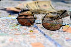 Sunglasses and money on a tourist map background. Tourism concept.  royalty free stock photo