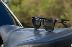 Sunglasses on motorcycle saddle. A pair of generic wayfarer sunglasses are on top of leather motorcycle seat. NOTE: Motorcycle property of photographer Stock Photography