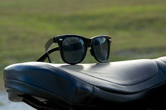 Sunglasses on motorcycle seat. A pair of generic wayfarer sunglasses are on top of leather motorcycle seat. NOTE: Motorcycle property of photographer Stock Photo