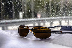 Sunglasses of a motorist for a bright sun, lie on the torpedo of a car. Royalty Free Stock Image