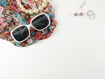 Sunglasses and necklaces made of pearls, placed on fashion veils and earrings royalty free stock photography