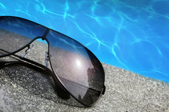 Sunglasses  next to a pool Stock Photography