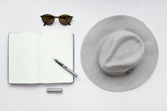 Sunglasses, notebook, pen, and hat, on white background Royalty Free Stock Images