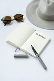 Sunglasses, notebook, pen, and hat, on white background Stock Photo