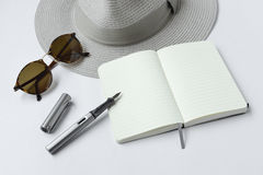 Sunglasses, notebook, pen, and hat, on white background Stock Photos