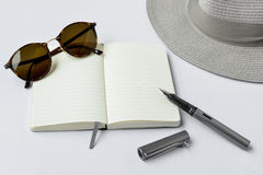 Sunglasses, notebook, pen, and hat, on white background Stock Images