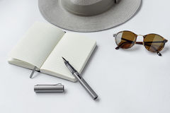 Sunglasses, notebook, pen, and hat, on white background Stock Image
