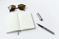 Sunglasses, notebook, and pen, on white background Royalty Free Stock Photography