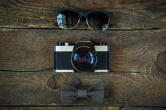 Sunglasses, old-fashioned camera and bow tie Stock Images