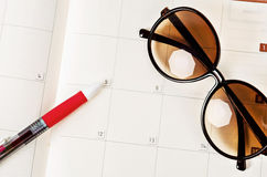 Sunglasses on open calendar page. Royalty Free Stock Images