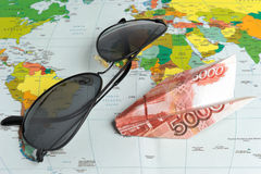 Sunglasses and origami plane made from money on the map Stock Images