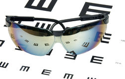Sunglasses over eye exam chart Royalty Free Stock Images
