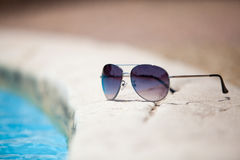 Sunglasses over swimming pool Royalty Free Stock Photography