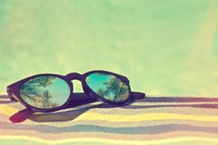 Sunglasses with palm trees reflections on a bath towel, summer concept. Sunglasses with palm trees reflections on a bath towel, vintage summer concept Stock Photo