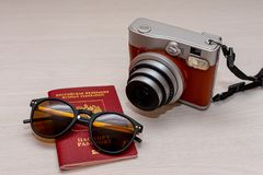 Sunglasses with the passport of a citizen of the Russian Federation and an instant photo camera on a white wooden background. Travel and vacation abroad concept stock photography