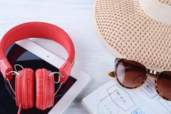 Sunglasses, passport, headphones, tablet and a hat. Royalty Free Stock Image