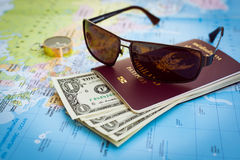 Sunglasses, passport, money and compass on the map Stock Photos
