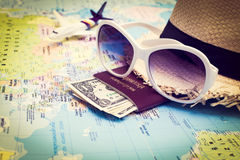 Sunglasses, Passport, Money, Hat and aircraft on the world map Stock Photos