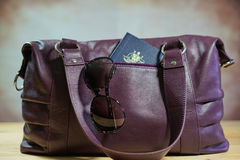 Sunglasses and passport in purple carry bag. Travel concept with sunglasses and passport in purple carry bag Stock Photo