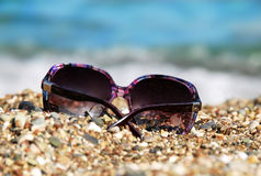 Sunglasses in pebble Stock Image