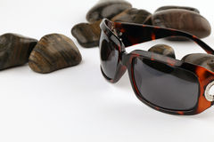 Sunglasses and pebbles Royalty Free Stock Photos