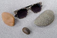 Sunglasses and pebbles on the sand Royalty Free Stock Images
