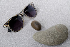 Sunglasses and pebbles on the sand Stock Photo