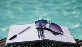 Sunglasses and pen on a note-pad. By the swimming pool Stock Images