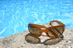 Sunglasses by Pool. Sunglasses on pool edge royalty free stock image
