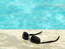 Sunglasses by the pool royalty free stock photos
