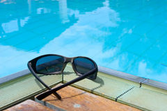 Sunglasses by the pool Royalty Free Stock Photography