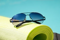 Sunglasses by the pool. Sunglasses on the yoga rug by the swimming pool Royalty Free Stock Image