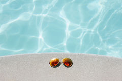 Sunglasses on poolside Royalty Free Stock Image