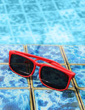 Sunglasses poolside in summer Stock Images