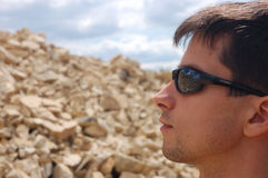 Sunglasses protect eye. Man with fashion sport sunglasses on the rock landscape background Royalty Free Stock Image