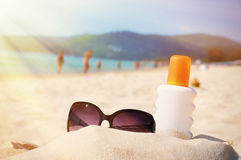 Sunglasses and protection lotion on the beach Royalty Free Stock Photos