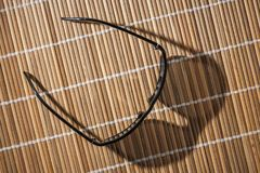 Sunglasses on reed mat from above. Sunglasses on a reed mat in top view with drop shadow Stock Photo